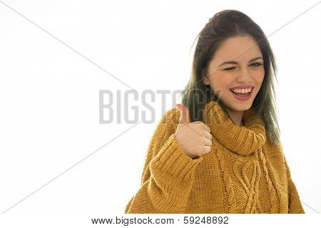 Enthusiastic attractive young woman winking and giving a thumbs up as she playfully gives her approval and agreement, isolated on white