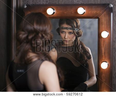 Mirror reflection of a young caucasian woman applying makeup