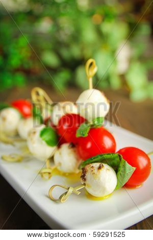 Delicious bocconcini, tomato and basil on toothpick.