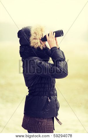 Woman standing outside and holding lorgnette in cold winter day.