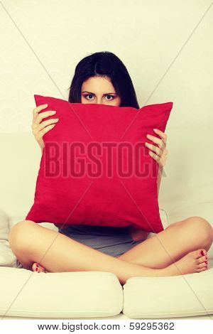 Scared young woman is waching tv. Brunette girl is sitting on the couch with red pilow and covering her face.