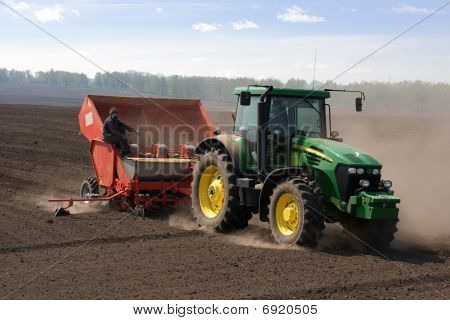 Tractor with seeding-machine (planter) on potato field (close view)