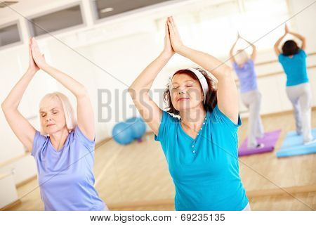 Portrait of two aged females doing yoga exercise in sport gym