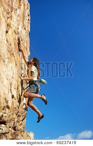 A rock climbing man reaching for a grip on a steep mountain in the outdoors