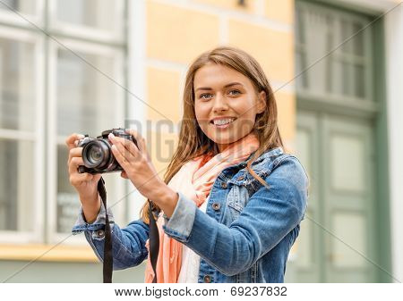 travel, vacation and technology concept - smiling girl with digital photocamera in the city
