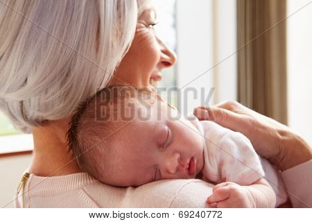 Grandmother Holding Sleeping Newborn Baby Granddaughter