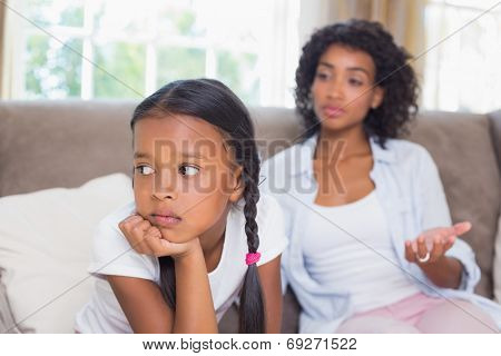 Pretty mother sitting on couch after an argument with daughter at home in the living room