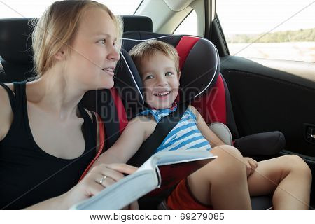 Mother reading a book to son in the car