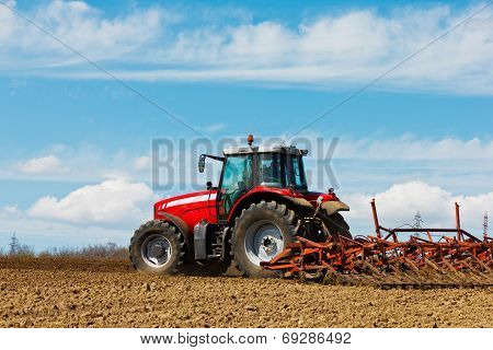 Farmer Plowing The Field. Cultivating Tractor In The Field. Red Farm Tractor With A Plow In A Farm F