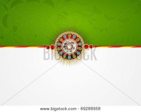 Beautiful rakhi on green and grey background on the occasion of festival Raksha Bandhan celebrations.