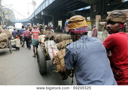 KOLKATA - FEB 15: Hard working Indians pushing heavy load through streets on February 15, 2014 in Kolkata, India. Human labour is still cheaper than motorised vehicles.