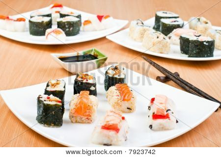 close-up of a plate with delicious sushi on and chopsticks on the side poster
