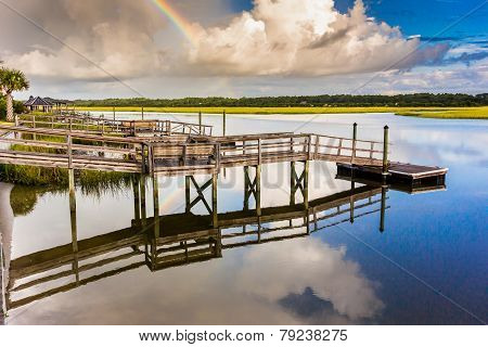 Rainbow And Docks Reflecting In Water