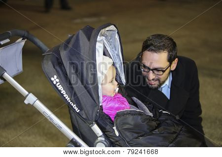 Child with father during menorah lighting
