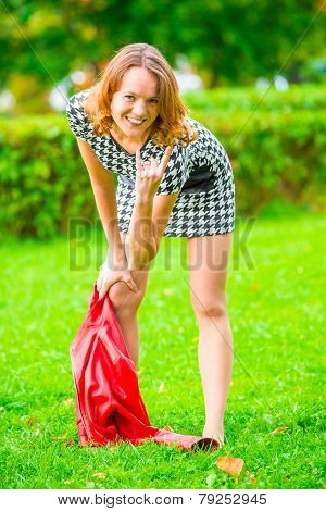 Impish Girl Posing On The Grass In The Park