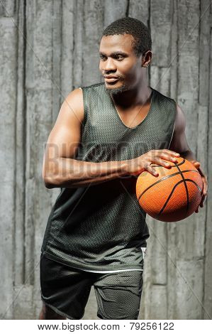 Afro-american young muscular male basketball player holding ball against grunge background poster