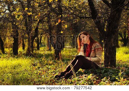 Young Woman With Long Red Hair Reading Under The Tree