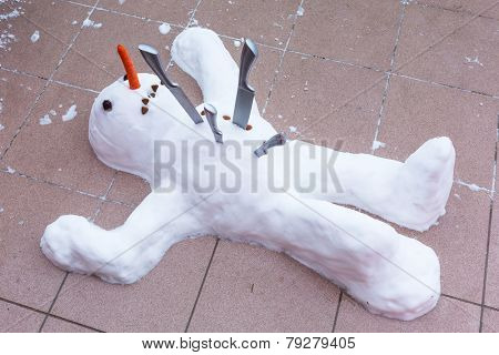Snowman lying down dead with knives in the chest. The end of winter symbol.