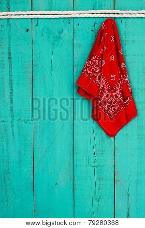 Red bandana hanging by rope border on antique blue wooden background