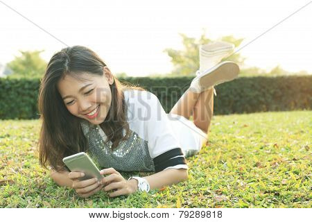 Portrait Of Beautiful Young Woman Lying And Playing And Watching To Smart Phone Screen In Home Garde