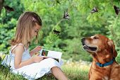 Little girl sits under a tree reading a book about butterflies as her faithful dog sits nearby watching butterflies fly around them. Butterflies are my own photos, including one in book. poster