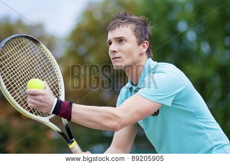Sport And Tennis Concept: Handsome Caucasian Man With Tennis Raquet Preparing To Serve Ball On Court