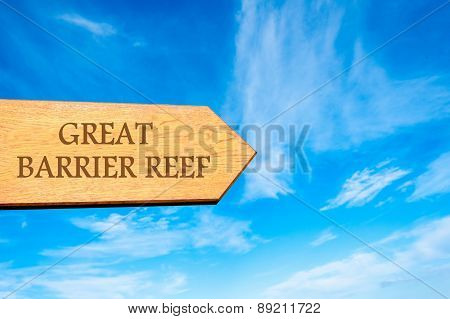 Wooden arrow sign pointing destination GREAT BARRIER REEF against clear blue sky with copy space available. Travel destination conceptual image poster