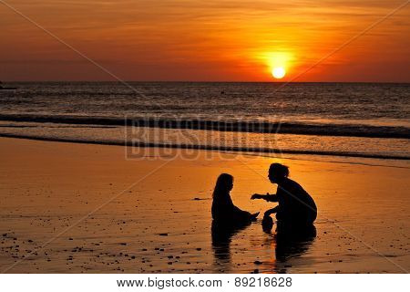 Silhouettes of little girl and mother at the beach during sunset