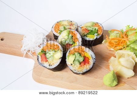 Set Of Vegetarian Sushi Rolls On A Wooden Plate Isolated On White Background