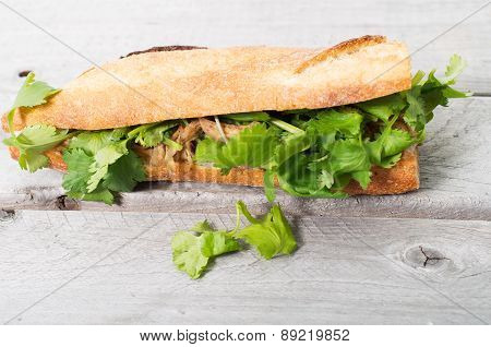 Banh Mi, Vietnamese Sandwich Filled With Shredded Chicken And Coriander On A Wooden Table