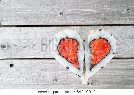 Two Pieces Of Sushi Forming The Heart Shape On A Wooden Background