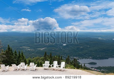 White Chairs On Top Of Mountain  At A Ski Resort During Summer Time Depicting Relaxing Concept