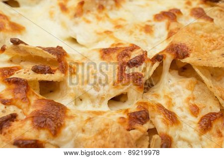 Tortilla chips covered with a thick layer of mozzarella cheese