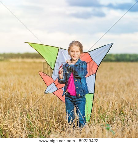 beautiful little girl witha kite in a field of wheat