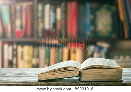 thick book on the table on the background of bookshelves poster