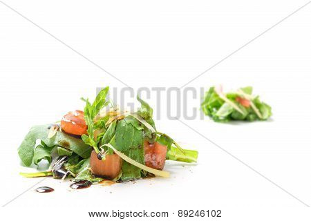 Small Heaps Of Rucola Salad With Tomatoes And  Parmesan Isolated On White