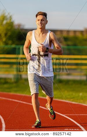 Young Athlete Running At The Running Track Holding A Stopwatch