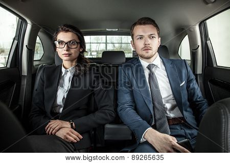 Businessman And Businesswoman Sitting In A Limousine
