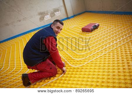 group of workers installing underfloor heating and colling in modern home