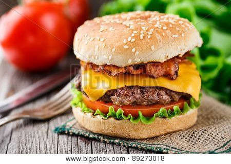 Bacon burger with grilled beef cutlet and tomato. poster