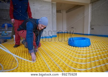 group of workera installing underfloor heating and colling in modern home