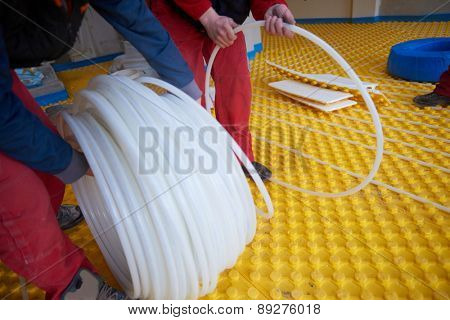 grouo of workera installing underfloor heating and colling in modern home