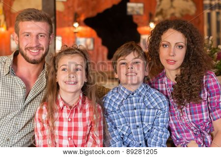 family of four closeup portrait on background of wall with pelts and photos