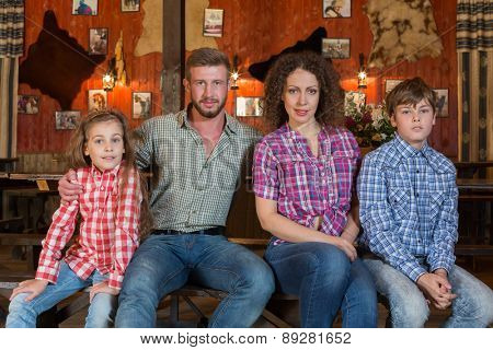 family of four sitting on a bench on background of wall with pelts