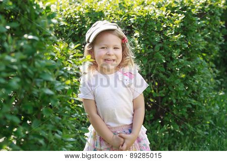 Two Year-old Laughing Girl In Corduroy Flat Cap At Green Garden Shrubbery Background