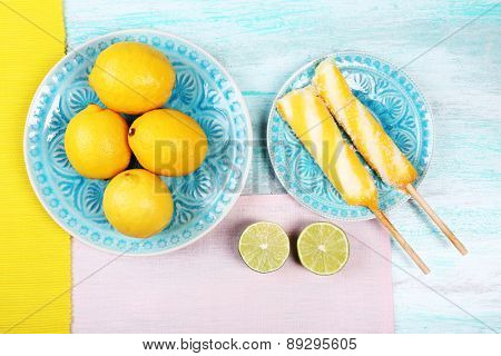 Lemons and ice cream on plates on table top view