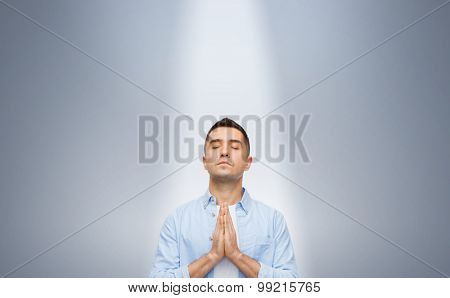 faith in god, religion and people concept - happy man with closed eyes praying under ray of ligh over gray background