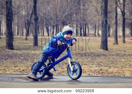 happy little boy on running bike in spring