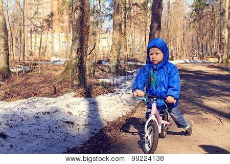 little boy riding runbike in winter