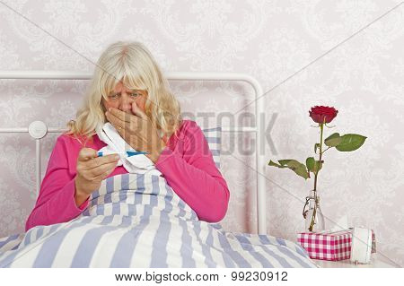 Sick Female In Bed Looking Worried At Thermometer